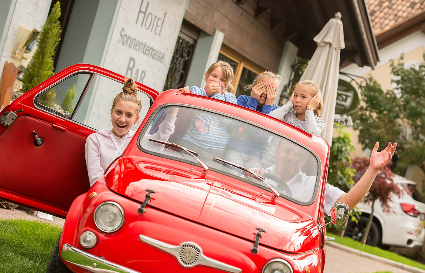 Four children in fun poses on a historic red vehicle in front of the Hotel Alpenhof in Saltusio
