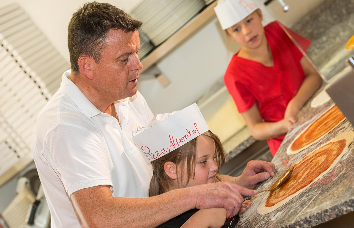 Chef teaches children the right way to distribute tomato on pizza