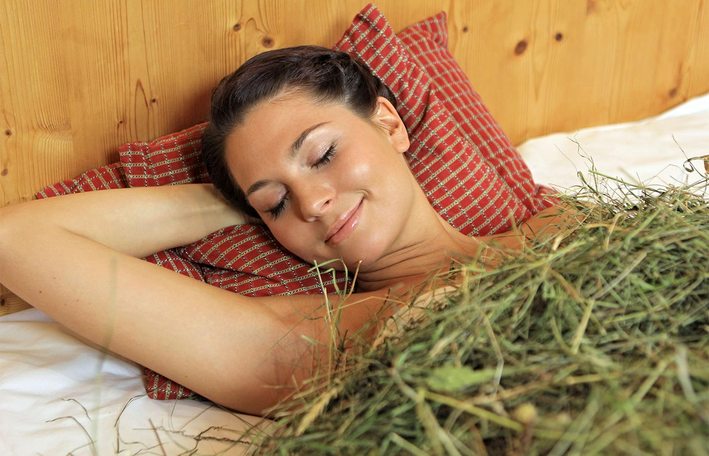Girl immersed in the hay bath enjoy a moment of well-being